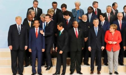 Emmanuel Macron jostles his way to the front of G20 photo to stand by Donald Trump